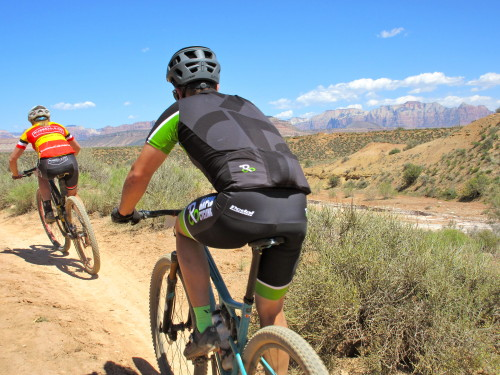 Riders on course with the towers of Zion National Park in the distance