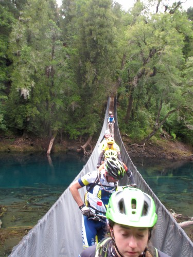 Riders crossing the first of many many suspension bridges at TransAndes. Riders were stuck on the bridge as a ramp at the far end made exiting the bridge very slow. We were later told the bridge had a maximum capacity of 5 people. Photo by: Shannon Boffeli