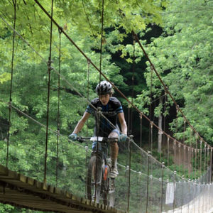 100-mile race winner Dylan Johnson successfully navigates a long suspension bridge. Photo by: Butch Phillips Photography
