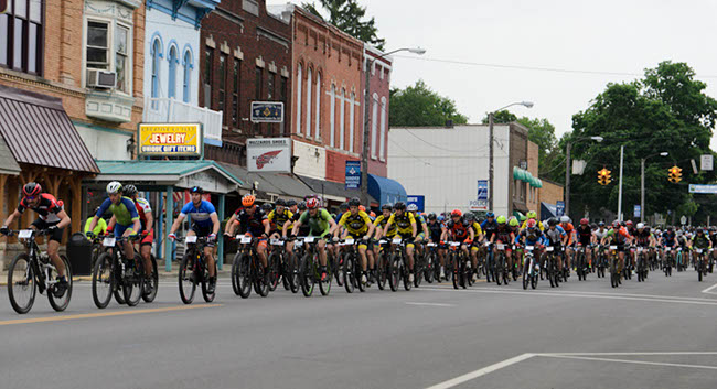 Hundreds of racers charge off the start line and through Loudonville, Ohio, at the start of the Mohican 100. Photo by: Butch Phillips Photography
